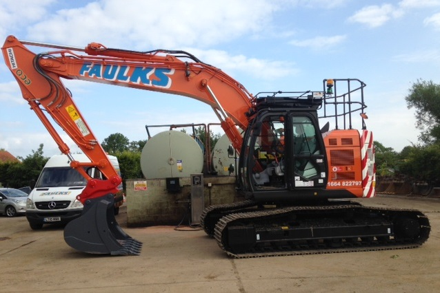 Orange Hitachi ZX225US tracked excavator in a car park at AE Faulks