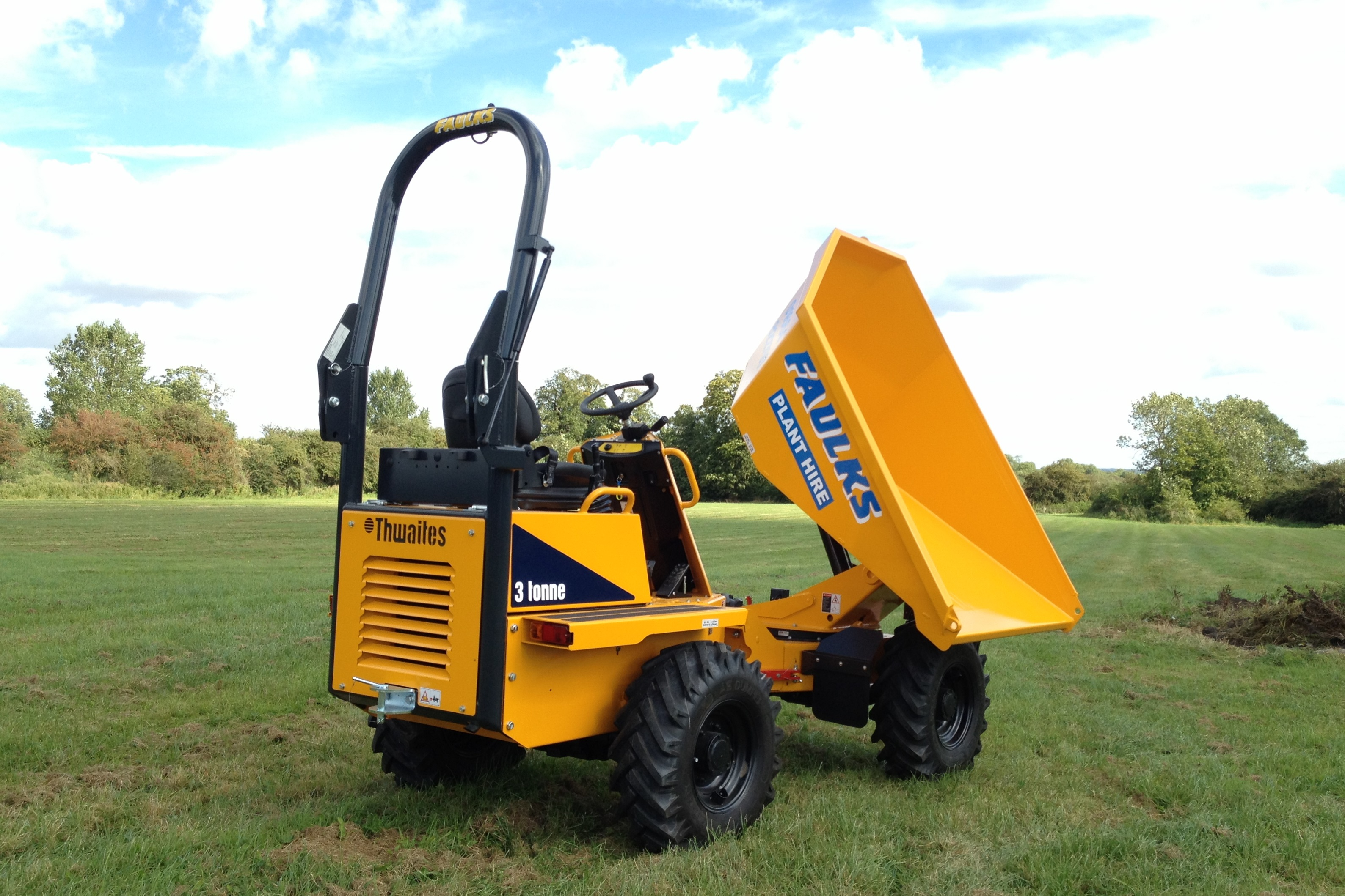 Small thwaites 3 tonne dumper in field with loader raised in topping position