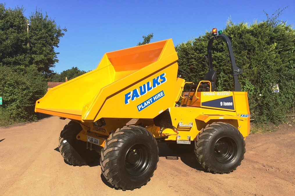 9 tonne dumper from Thwaites in field in front of bushes. One example of front loader dumper hire from AE FAulks