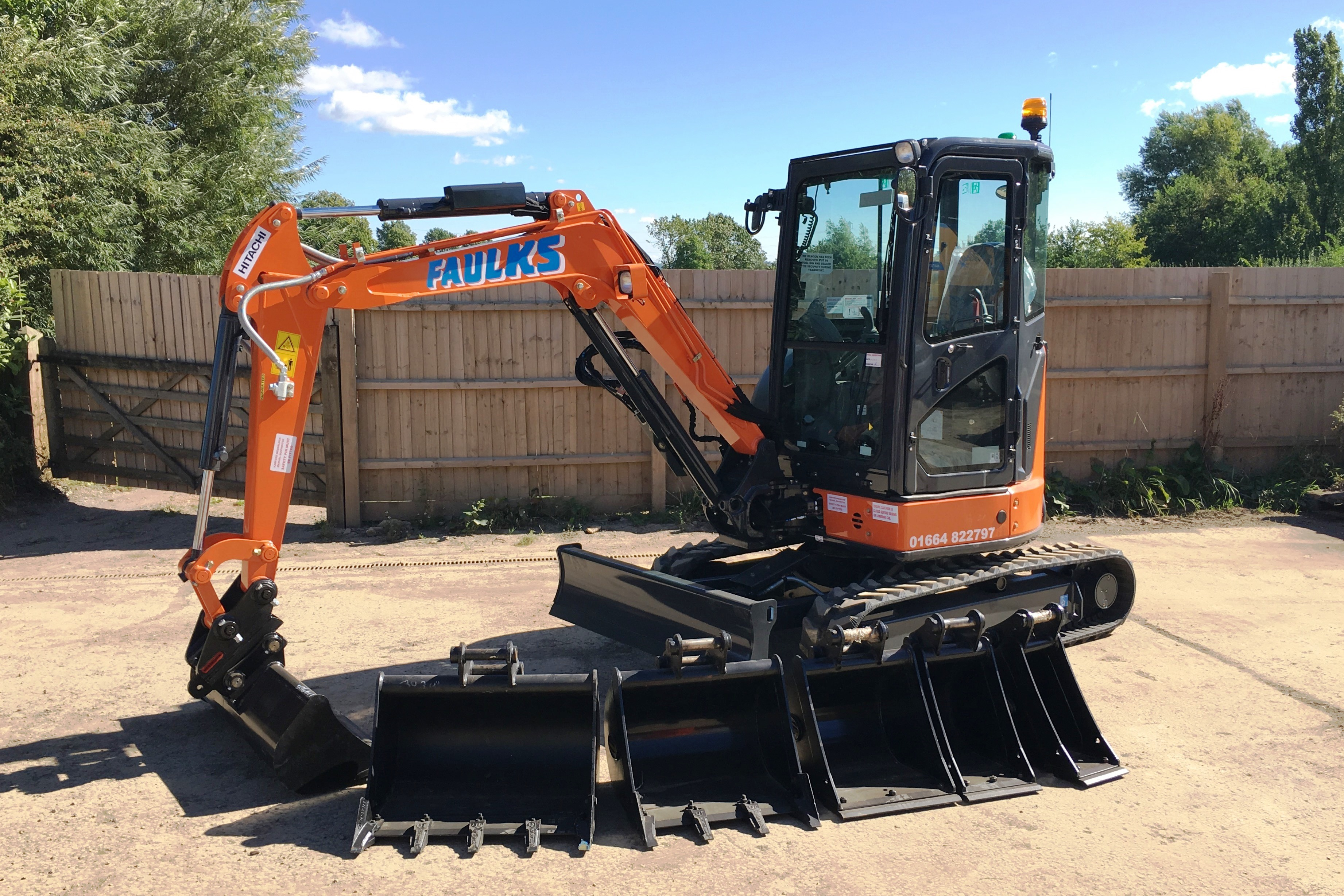 The Hitachi ZX33 tracked excavator in car park with digger head options lined up, side view