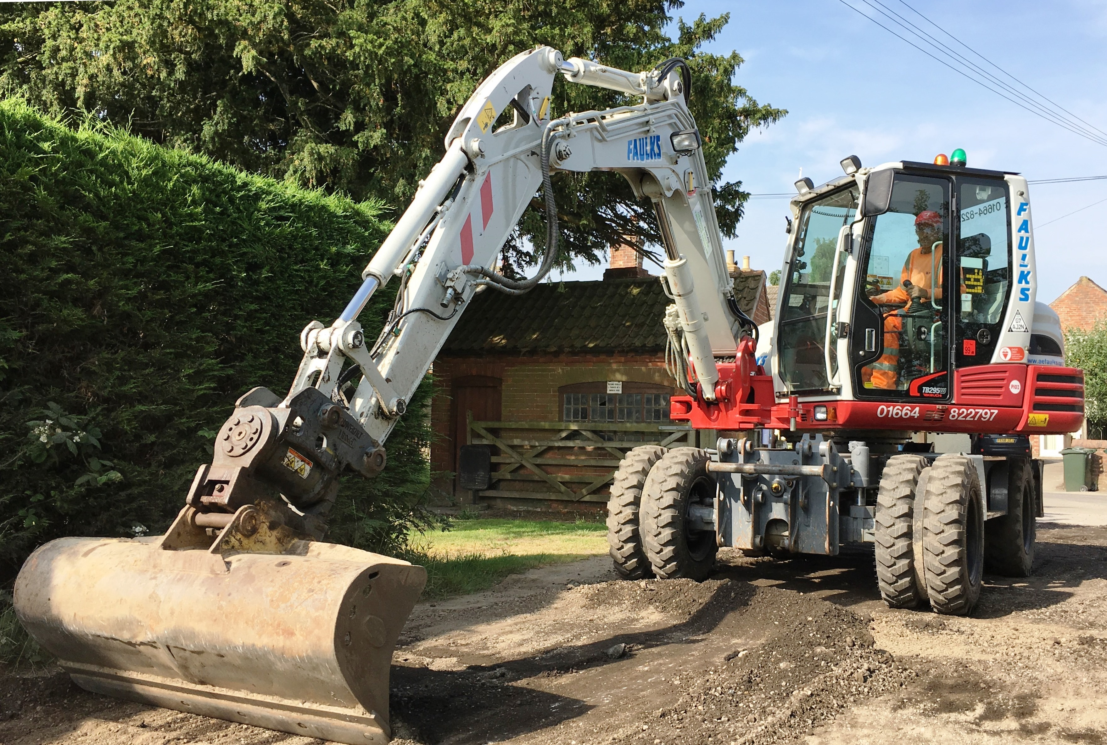 Takeuchi wheeled excavator in use on driveaway