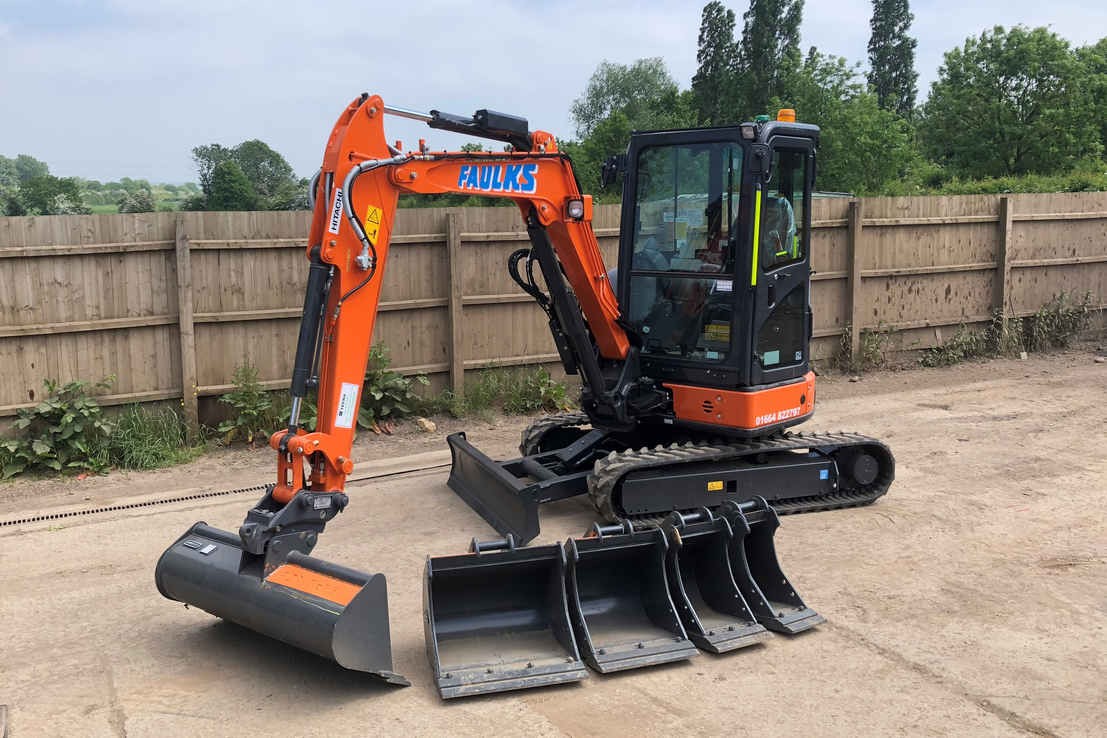 The Hitachi ZX33 tracked excavator in car park with digger head options lined up