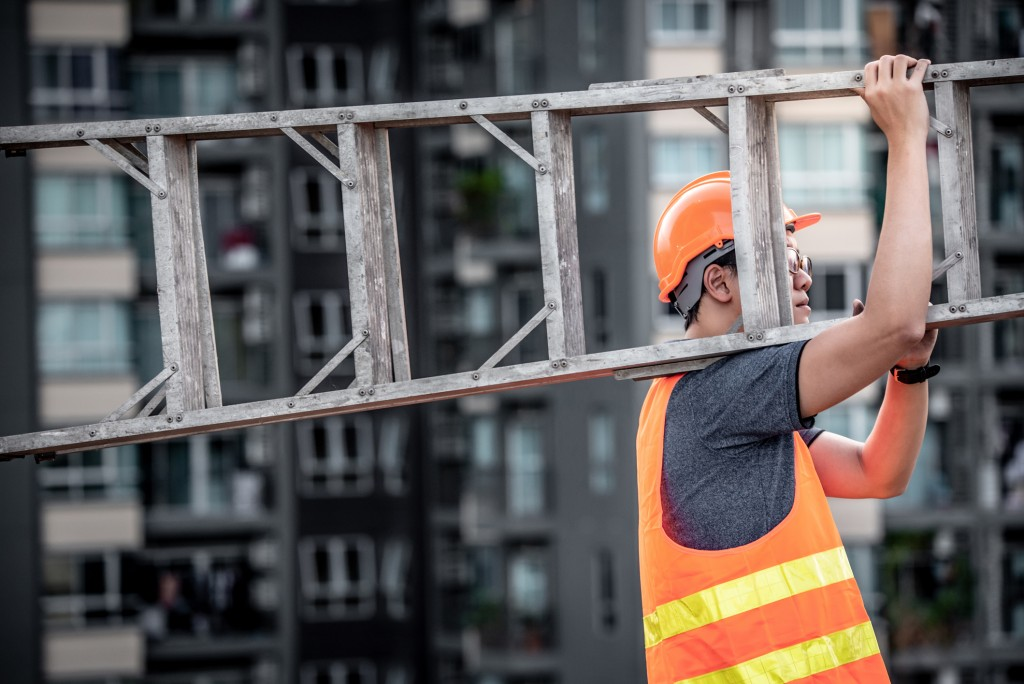 Maintenance worker with orange safety helmet and vest carrying aluminium step ladder at construction site.
